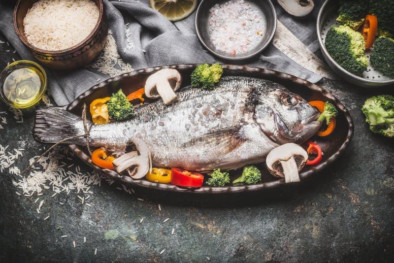 Rybi naczynie z ryż i warzywami na nieociosanym tle, odgórny widok fotografia royalty free