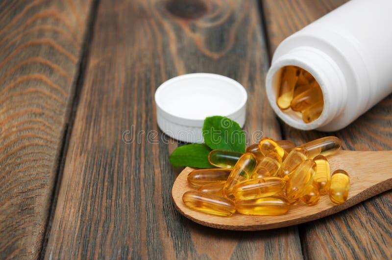 Rybiego oleju kapsuły w łyżce obrazy stock