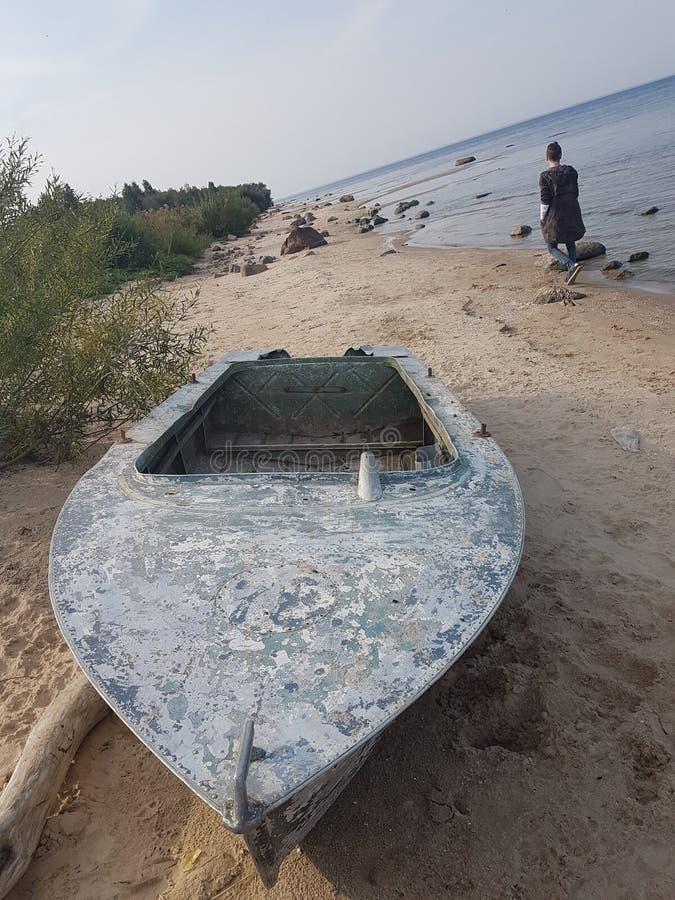 Rybinsk-Reservoirufer mit einem Boot auf dem Ufer und einem Fischer von der Rückseite, Yaroslavl-Region, Russland stockbild