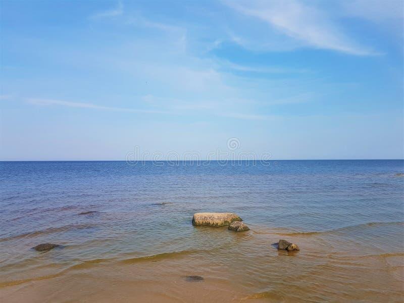Rybinsk rezerwuaru brzeg z łodzią na brzeg i rybakiem od plecy, Yaroslavl region, Rosja obrazy stock
