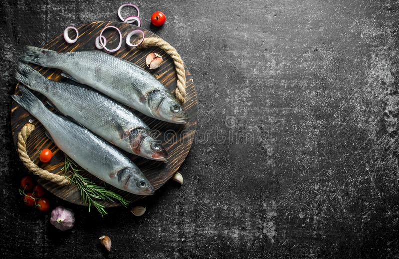 Ryby surowe na tacce z cebulą w plasterkach, rozmarynami i pomidorami zdjęcia stock