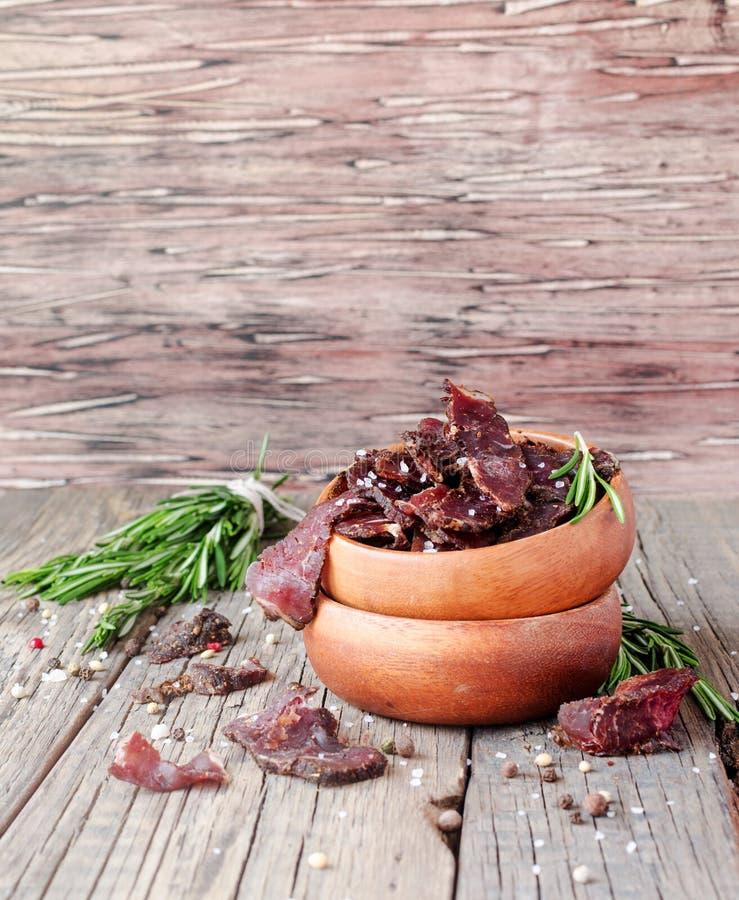 Ryckt till kött, ko, hjortar, löst fä eller biltong i träbunkar på en lantlig tabell, selektiv fokus arkivbild