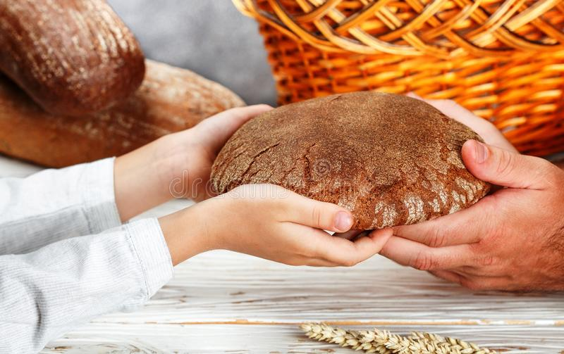 Rye black bread in his hands. A child gives a loaf to a man. The Rustic style. Selective focus stock image