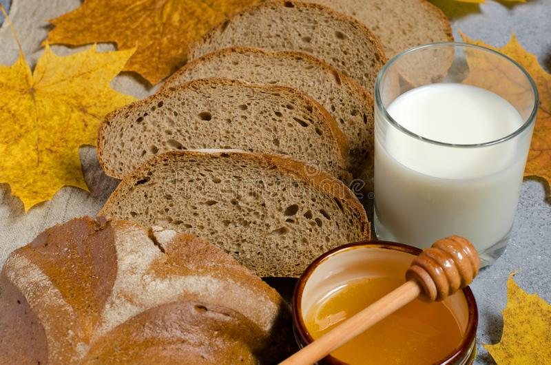 Rye bread is cut into pieces. Honey, milk in a glass Cup, yellow maple leaves.  royalty free stock image