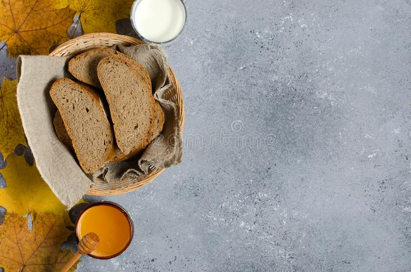 Rye bread is cut into pieces. Honey, milk in a glass Cup, yellow maple leaves. Traditional rural food. Copy space.  royalty free stock image