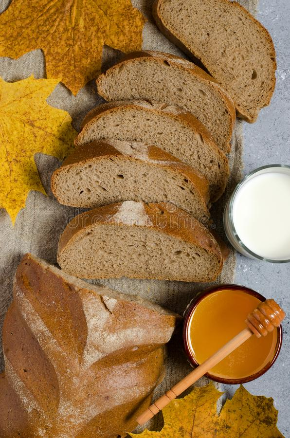 Rye bread is cut into pieces. Honey, milk in a glass Cup, yellow maple leaves. Traditional rural food. Vertical photo.  stock image