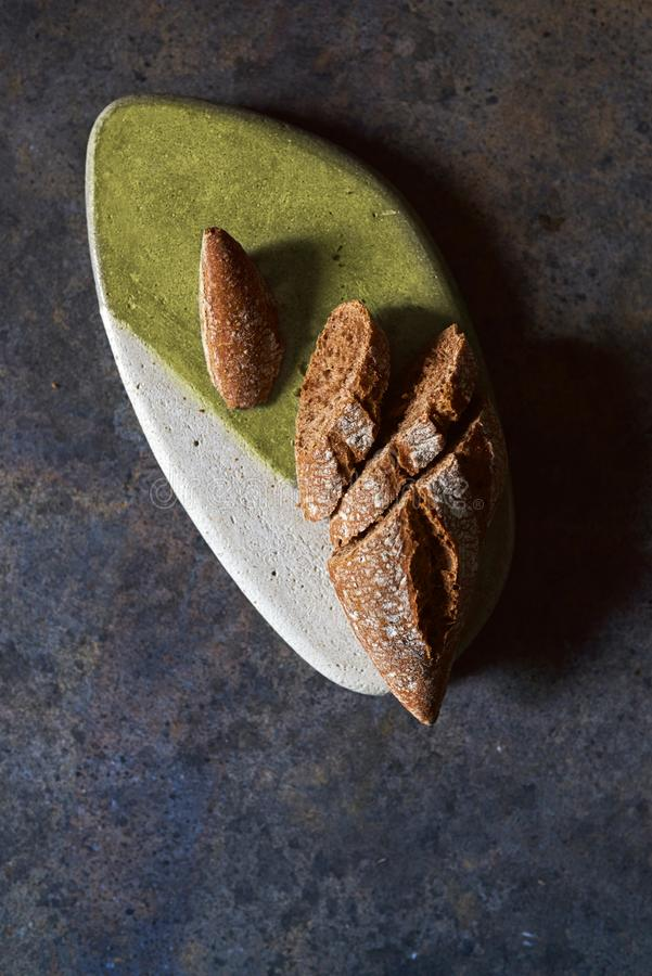Rye bread, cut into slices. On stone table on grunge background stock image