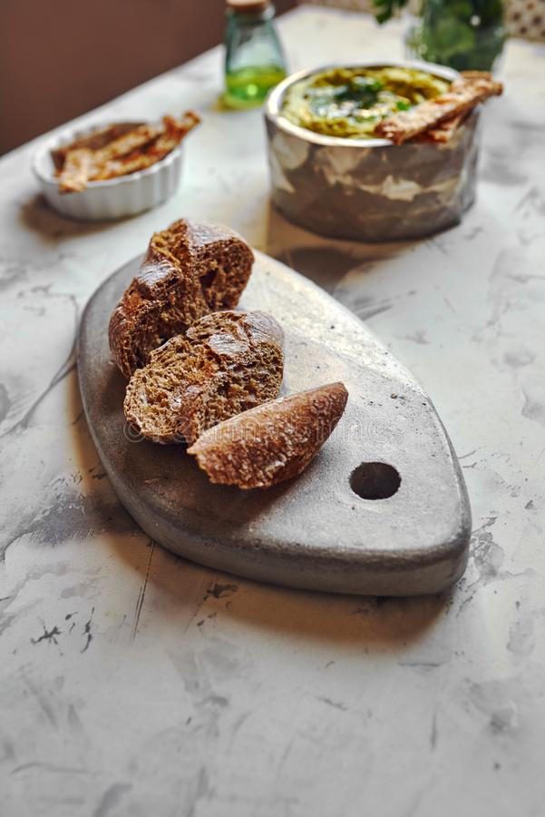 Rye bread, cut into slices. On stone table on the table set stock photo