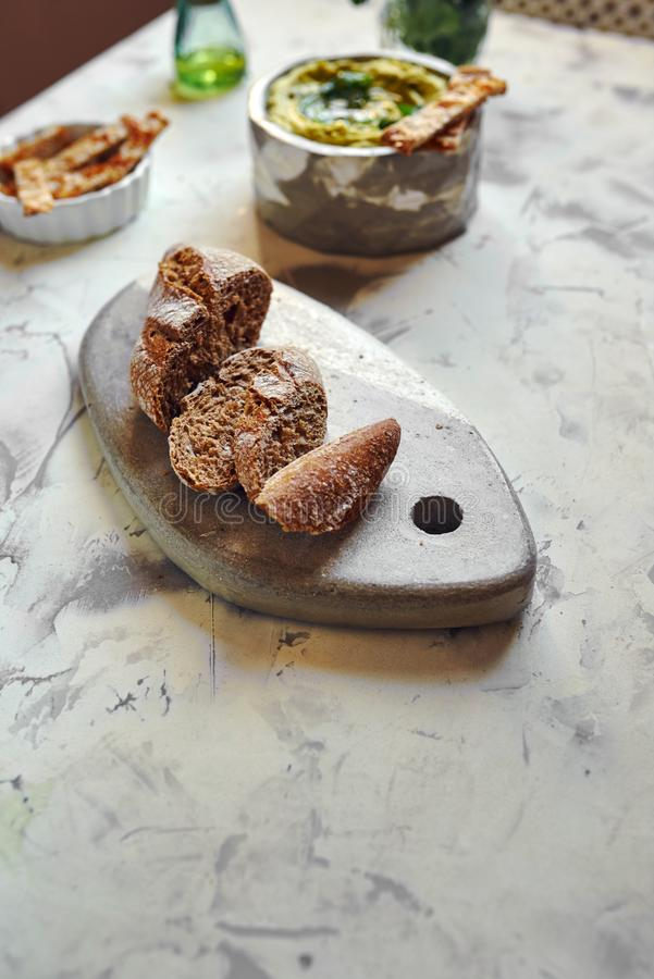 Rye bread, cut into slices. On stone table on the table set stock photos