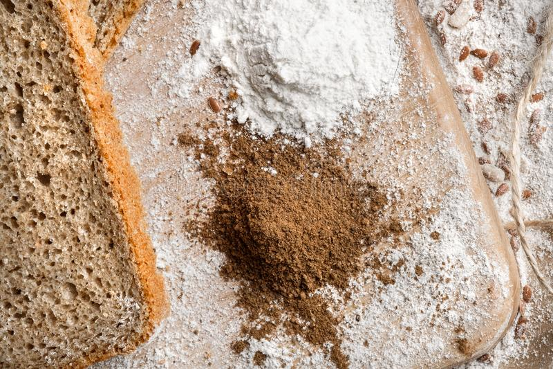 Rye bread on malt and flour, lies on the table. Near a pinch of flour and malt. stock image