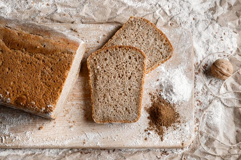 Rye bread on malt and flour, lies on the table. Near a pinch of flour and malt. royalty free stock image