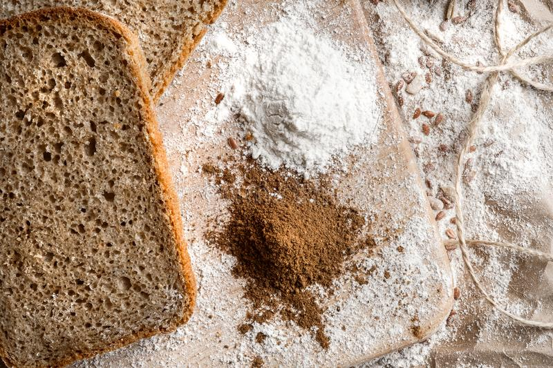Rye bread on malt and flour, lies on the table. Near a pinch of flour and malt. royalty free stock photo
