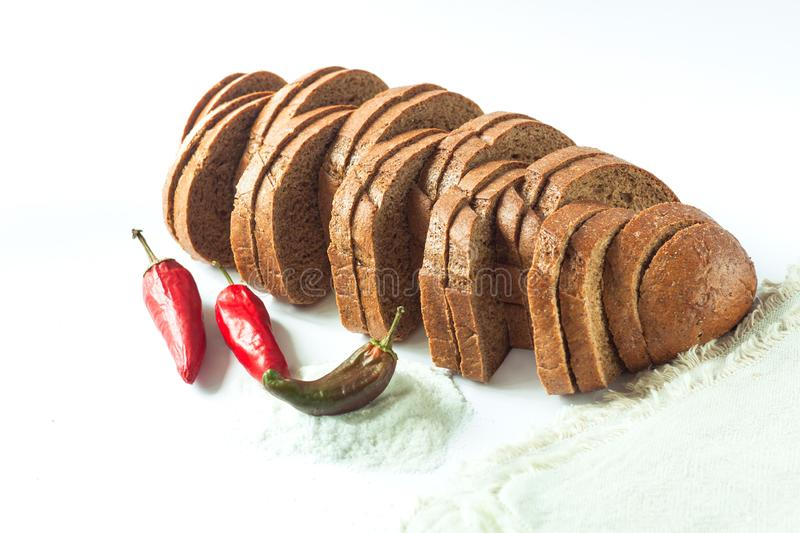 Rye bread with red chili peppers and salt on a white background isolated. Chopped bakery products made with various flours from grain. A loaf sliced into stock photo