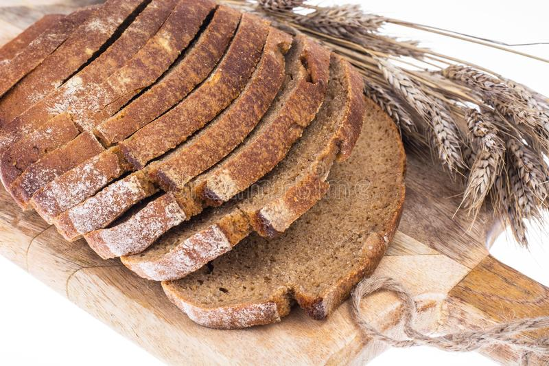 Rye bread, sliced on a kitchen wooden board, ears with grains royalty free stock images