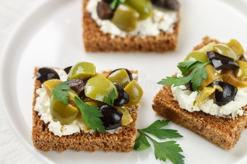 Rye bread toast canape with black and green olives, feta chees. E and parsley. Tasty snack for gourmets. Selective focus stock images