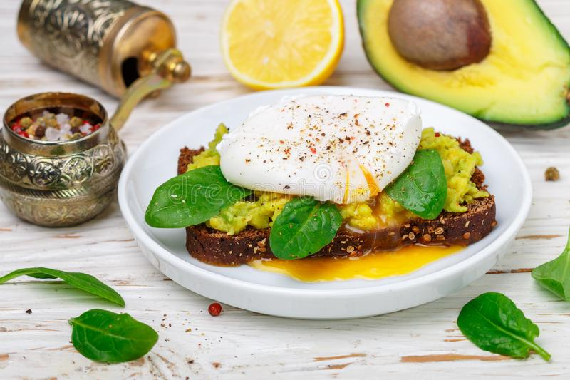 Rye Bread Toast with coriander, Poached Egg with Green Salad spinach , Avocado guacamole, lemon and spices stock images