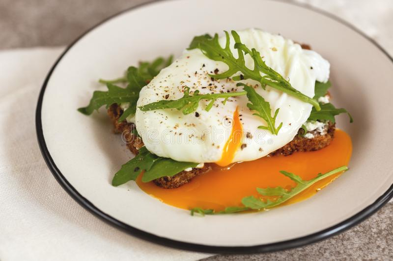 Rye toast with poached egg, dairy cream and arugula stock photo