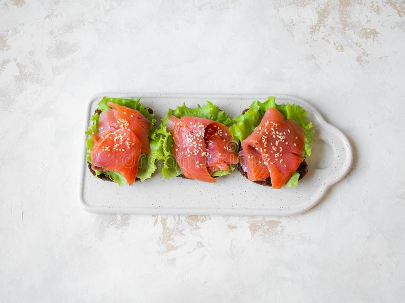Rye bread toasts with salmon slices, sesame and lettuce on a white ceramic plate on grey background. Top view. Copy space stock images