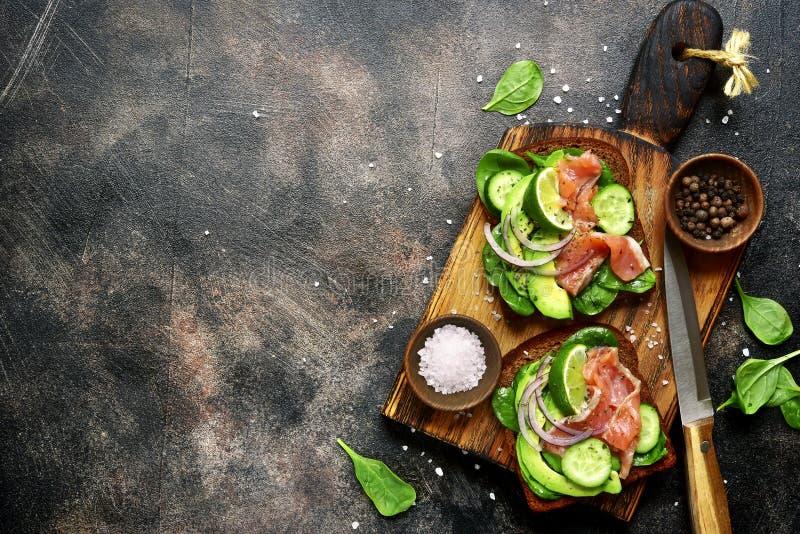 Rye brinda com abacate, pepino, salmões, e espinafres Sagacidade da vista superior fotos de stock royalty free