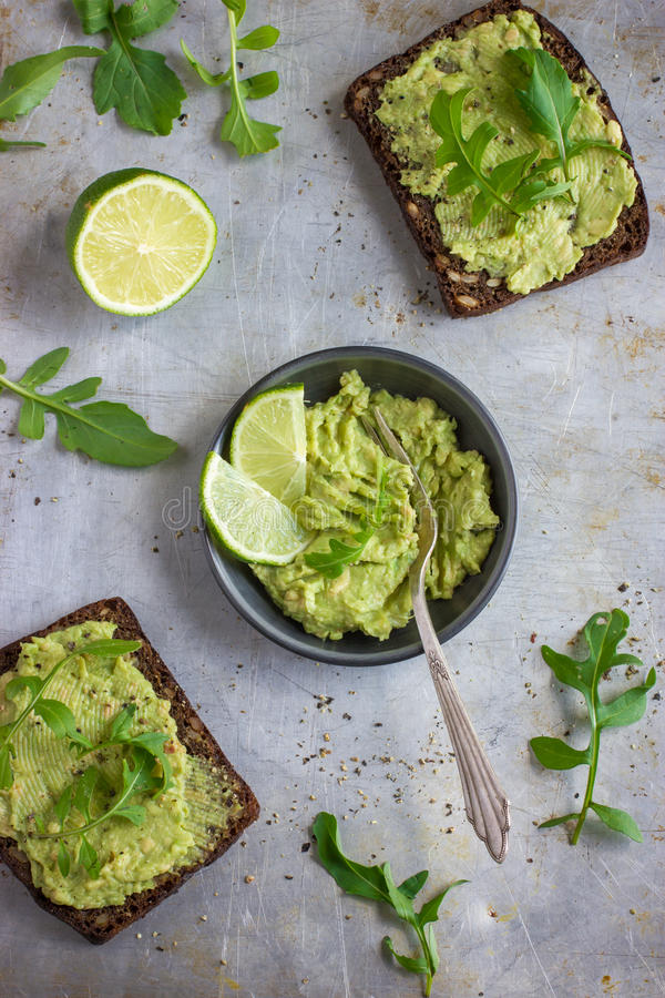 Rye brinda com guacamole e rúcula no fundo rústico foto de stock royalty free