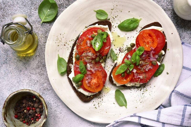 Rye brinda com queijo macio, tomate, a cebola vermelha e as alcaparras parte superior vi fotografia de stock