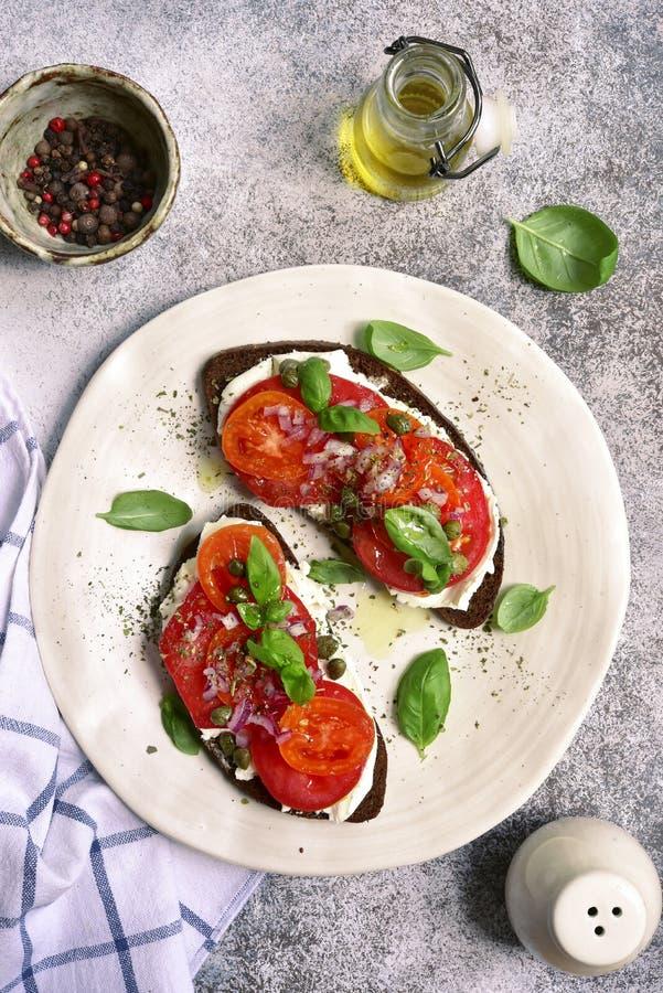 Rye brinda com queijo macio, tomate, a cebola vermelha e as alcaparras parte superior vi fotos de stock