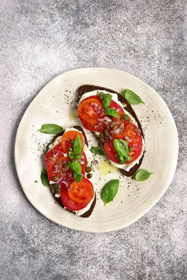 Rye brinda com queijo macio, tomate, a cebola vermelha e as alcaparras parte superior vi fotos de stock royalty free