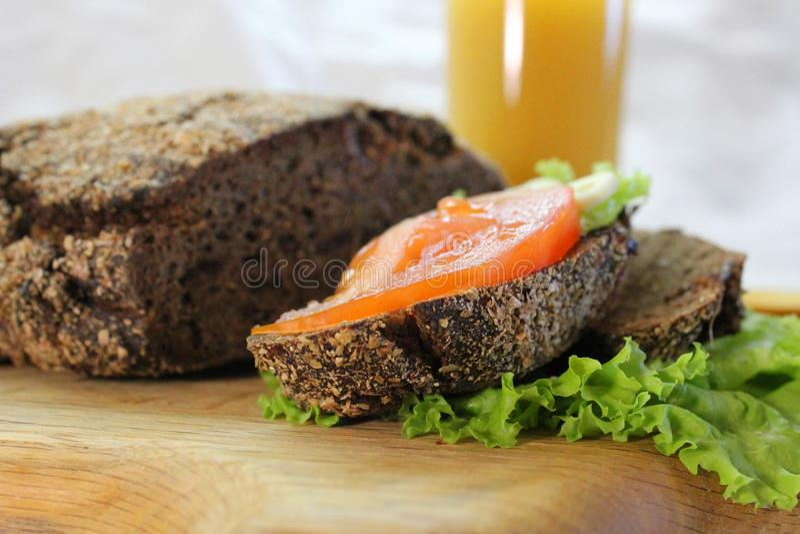 Rye-Brot mit Kopfsalat und Tomate auf dem hackenden Brett stockbilder