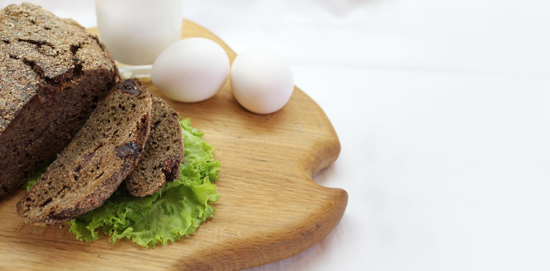 Rye-Brot mit Salatblättern, Eiern und einem Glas Milch auf einem Schneidebrett mit freiem Raum für Text lizenzfreie stockfotos