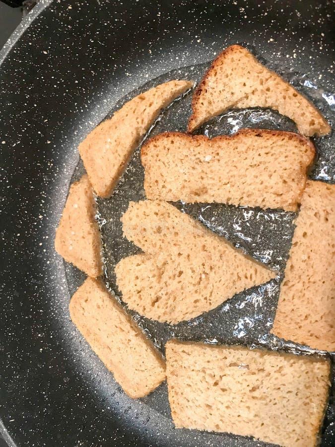 Rye-Brot wird in einer Bratpfanne im Öl, Croutons, suhariki in Form von Herzen gebraten lizenzfreie stockfotos
