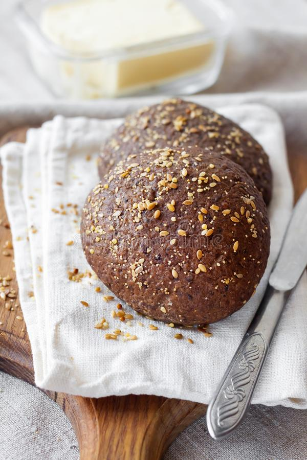 Rye buns with linseeds, sesame and white poppy seeds on wooden board royalty free stock photography