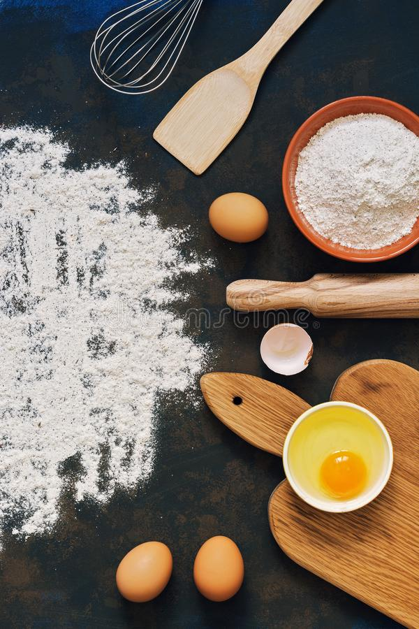 Rye flour, rolling pin, whisk, paddle, eggs, cutting board.Ingredients for baking rye bread. View from above. Place for text. royalty free stock photos