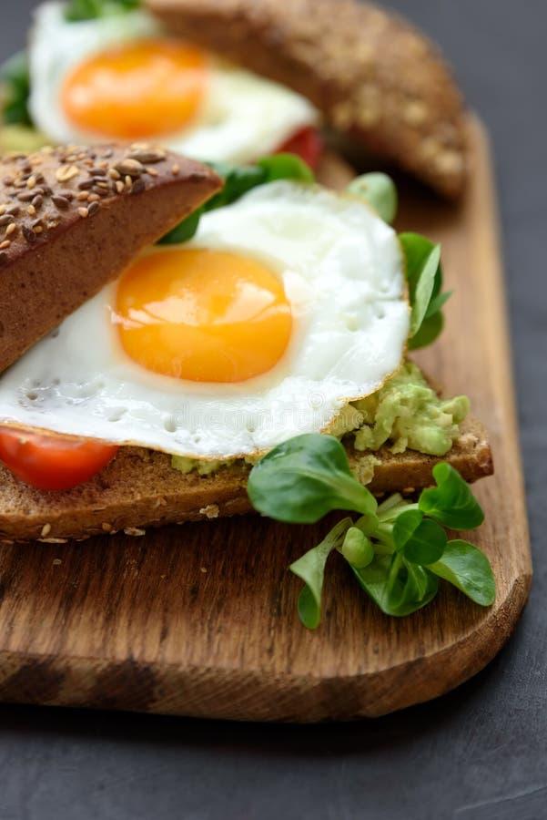 Rye imprensa hamburgueres com abacate, tomate, ovo frito e verdes no fundo de madeira marrom Foco seletivo Comer saudável ou foto de stock royalty free
