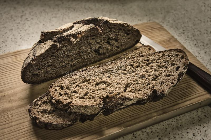 Rye organic bread cut over a wood table. Rye organic bread cut and sliced over a wood table with the knife royalty free stock photo