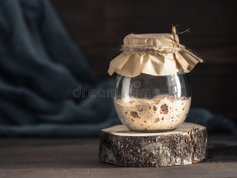 Rye sourdough starter. Active rye sourdough starter in glass jar on brown wooden background. Starter for sourdough bread. Toned image. Copy space royalty free stock photos