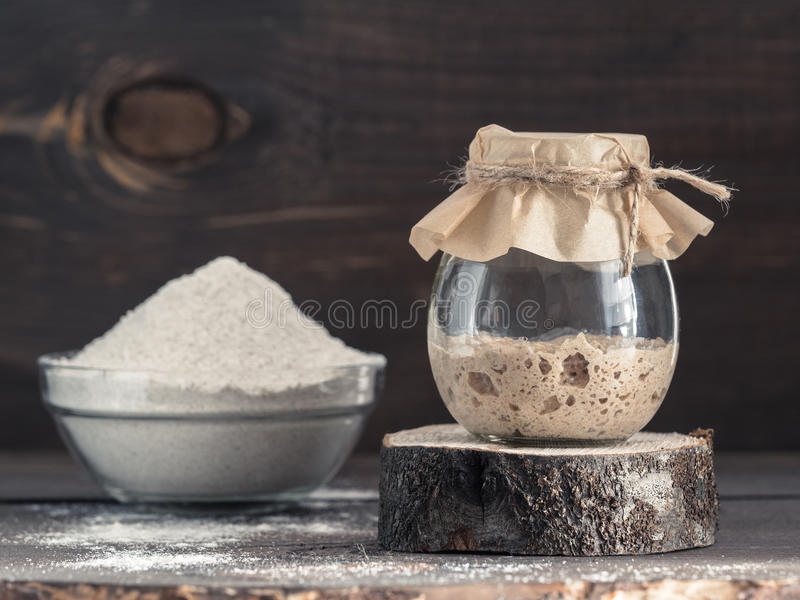 Rye sourdough starter and rye flour. Active rye sourdough starter in glass jar and rye flour on brown wooden background. Starter for sourdough bread. Toned image stock images