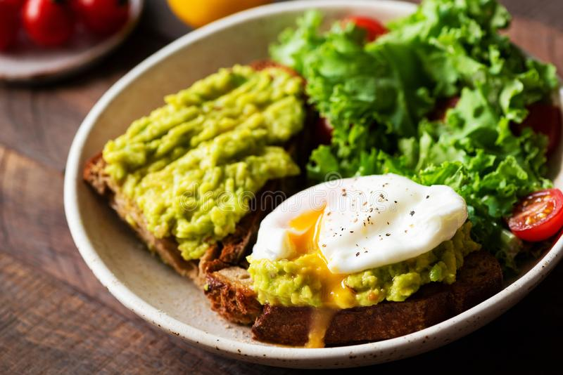 Rye toast with avocado cream and poached egg royalty free stock images