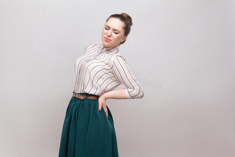 Ryggen eller njuren smärtar Stående av den härliga unga kvinnan i randig skjorta och grön kjol och den samlade förbudfrisyren, an royaltyfria foton