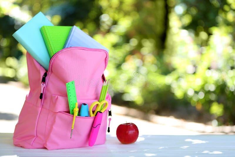 Ryggsäck med skolabrevpapper på tabellen royaltyfri foto