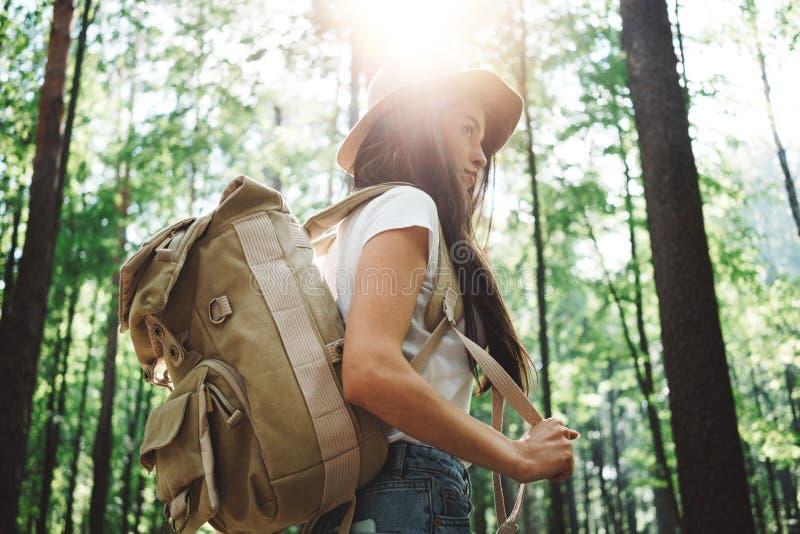 Ryggsäck och hatt för modig hipsterkvinna som bärande bara reser bland träd i skog på utomhus royaltyfri bild