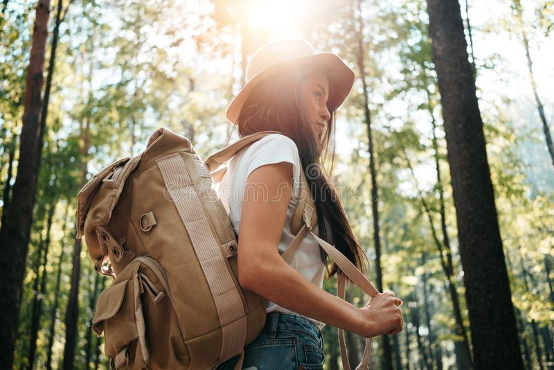 Ryggsäck och hatt för ung handelsresandekvinna bärande i hand bland träd på solnedgången Hipsterflicka med resanderyggsäcken i sk arkivfoto