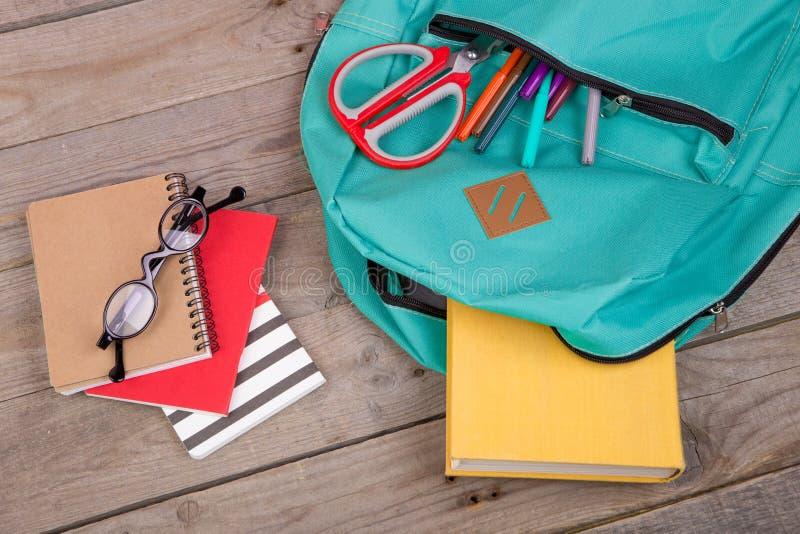 Ryggsäck- och skolatillförsel: böcker blyertspennor, notepad, tuschpennor, glasögon, sax på trätabellen royaltyfria bilder