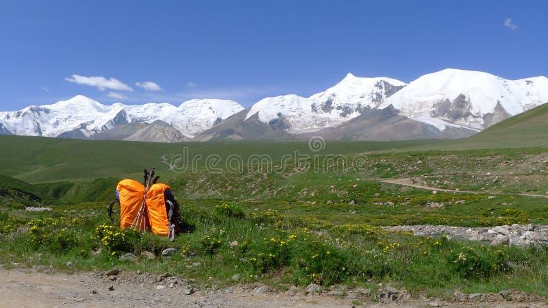 Ryggsäckar och heligt snöberg Anymachen på tibetan platå royaltyfri fotografi