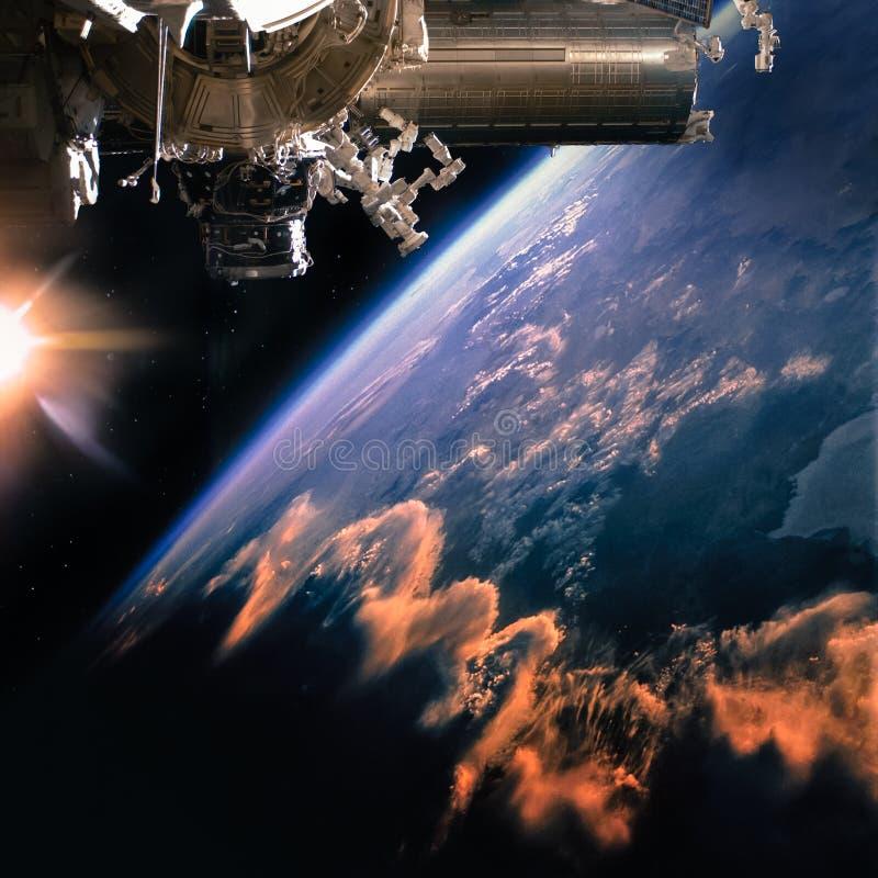 Rymdskepp på omloppet Jord med molnsolsken på bakgrunden fotografering för bildbyråer