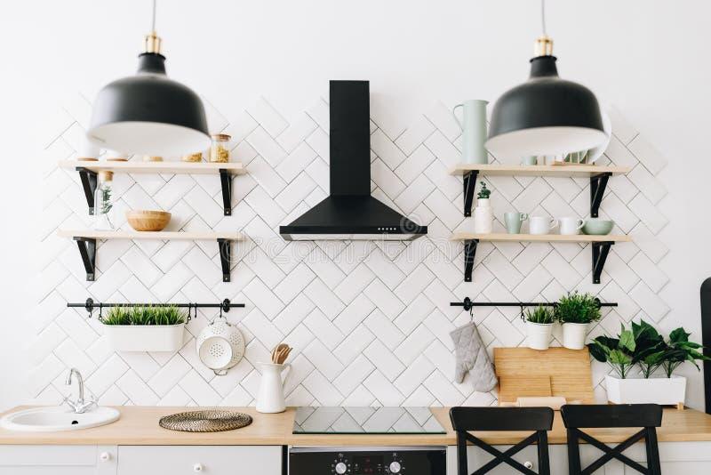 Rymligt modernt skandinaviskt vindk?k med vita tegelplattor och svarta anordningar ljus lokal inre modernt arkivfoton