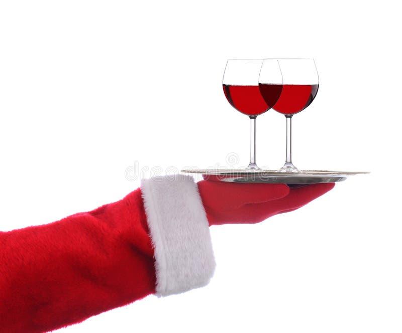 Rymma för Santa Claus utsträckt arm ett tjänande som magasin för silver med två exponeringsglas av rött vin över en vit bakgrund royaltyfria foton
