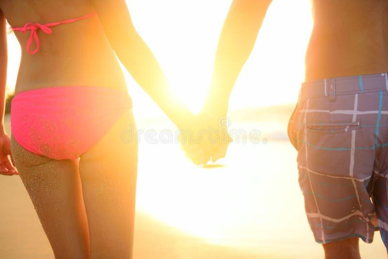 Rymma händer koppla ihop förälskat koppla av på stranden royaltyfri bild