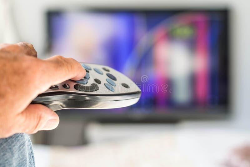 Rymma och peka en TVfjärrkontrollask på en television arkivbilder
