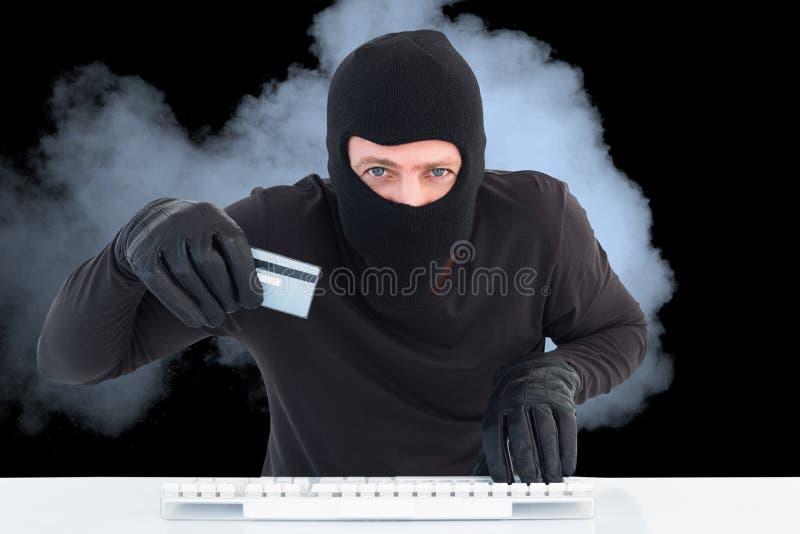 Rymmer den bärande huven för en hacker en kreditkort i röken mot svart bakgrund royaltyfria foton