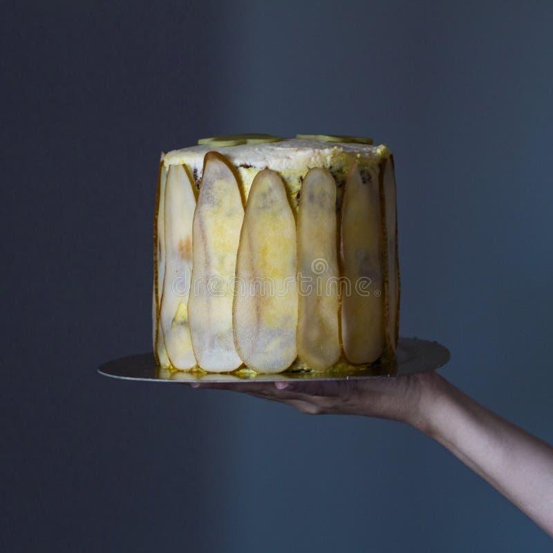 Rymmer den höga kakan för den hemlagade moroten som dekoreras med päronskivor, flickan över magasinet på en grå bakgrund arkivbild